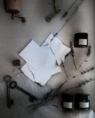 Sheets burnt paper, cans and bottles, old keys, dry lavender. top view