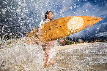 Wall Mural - Surfing girl with surfboard in water splashes