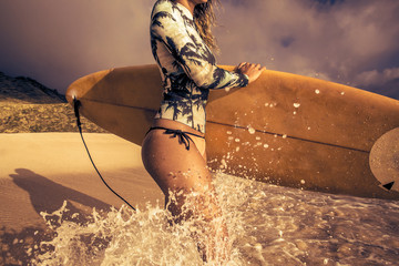 Surfing girl with surfboard in water splashes