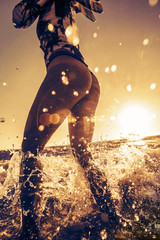 Beach girl stand in splashes in water. Model hold small fins in