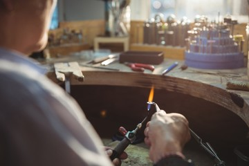 Craftswoman using blow torch in workshop