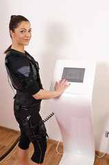 Beautiful girl posing next to muscle stimulation machine preparing to workout