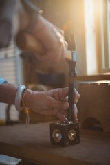 Hands of craftswoman using hammer