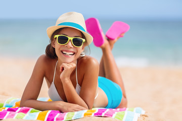 Summer woman relaxing in hipster beach hat and colorful sunglasses. Funky happy girl having fun during travel holidays vacation. Young trendy cool hipster woman in bikini lying in the sand.