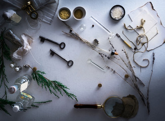 jars of powders, leaves burnt paper, magnifier, scales on the table. top view