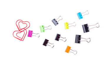 Follow the heart made by multicolored paper clip binders isolate