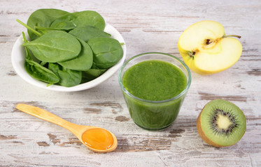 Ingredients and fresh cocktail from spinach, apple and kiwi on wooden background, healthy nutrition