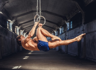Athletic gymnast exercising on stationary rings.