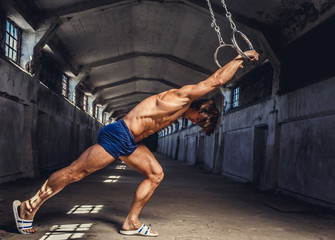 Athletic muscular male posing with gymnastic rings in a dark ind