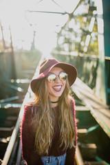 Girl in sunglasses laughing on railway bridge.