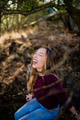 Girl laughing in forest.