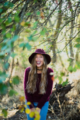 Extravagant laughing woman lauging in forest.