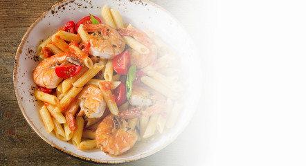 Penne pasta with shrimp and tomatoes  on rustic wooden table.