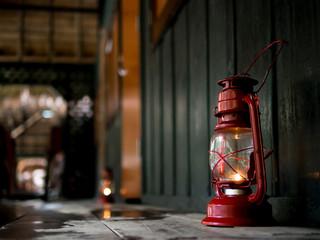shot focus on a red old lantern on the dark wet wooden floor wit
