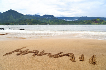Hawaii word written on sand on hawaiian beach. Handwriting text texture on holiday background. Famous destination Hanalei bay in Kauai, USA with ocean and mountains.