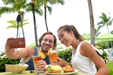 Happy young interracial couple on summer holiday going out for dinner enjoying local food meal at outdoor terrace restaurant taking a selfie picture with mobile phone for vacation memories.
