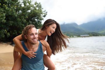 Two young people playing having fun laughing in love. Interracial couple piggybacking, boyfriend carrying Asian girlfriend doing piggyback on hawaiian beach in Kauai, Hawaii travel vacation.