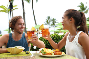 Fotobehang - Happy multiracial couple toasting cheers with alcoholic hawaiian drinks, mai tai, Hawaii experience. Summer travel holidays, people enjoying local food meal at outdoor terrace restaurant of resort.