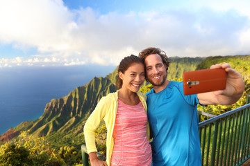 Happy interracial travel couple taking selfie mobile phone picture at Kalalau lookout on na pali coast viewpoint in Kauai, Hawaii with amazing scenic landscape. Famous popular hawaiian attraction.