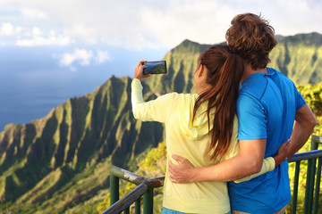 Wall Mural - Couple on travel destination vacation relaxing together. Happy young adults tourists taking pictures with smartphone of amazing scenic view of na pali coast at Kalalau lookout on Kauai, Hawaii, USA.