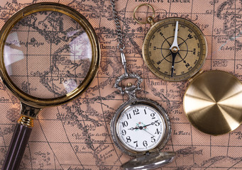 top view, vintage marine compass, pocket watch and magnifying glass on old map, close-up