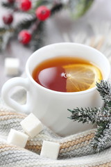 Cup of hot tea with lemon and woolen scarf