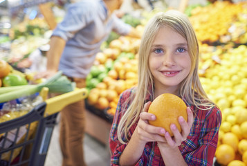 Girl holding orange in grocery store
