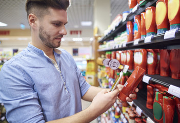 Man checking product on smartphone in store