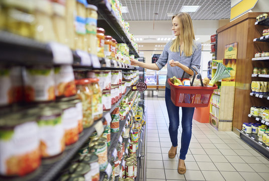 Woman buying products in food aisle