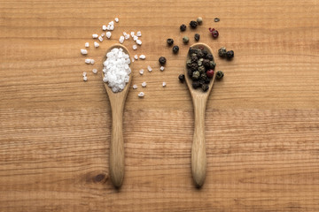 salt crystals and color pepper on wooden spoons on wooden table