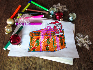 Child's drawing of Santa Claus with a gift. Holiday decorations