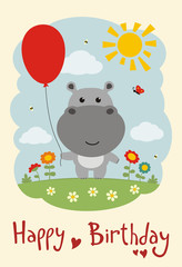 Happy birthday! Funny hippo with balloon on flower meadow. Card in cartoon style.