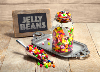 Stylized display of assorted flavor Jelly bean candies in a jar with scoop and signage on a wooden surface