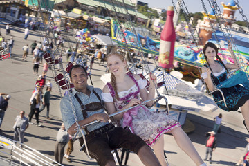 Couple having fun on chain carousel at Oktoberfest