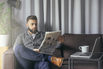 Young bearded businessman, dressed in white shirt, gray cardigan and blue pants, sitting in a room on a brown couch and reading a newspaper. Next to the glass table is a laptop and a cup of coffee.