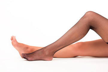Female legs on white background. Black fishnet stocking. Beauty and sensuality. Make impression on men.