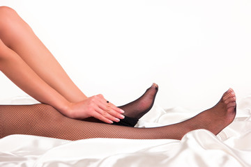 Lady puts on stockings. Black fishnet tights. Be attractive and irresistible. Silk and skin.