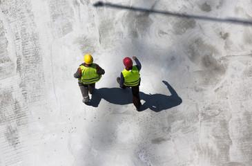 zwei Bauarbeiter auf Betongründung