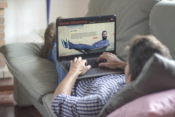 Young man lying comfortably on the sofa while using the laptop with series streaming website on the screen. View from behind. All screen graphics are made up.