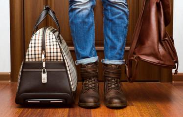 Девушка в джинсах и кожаных ботинках с рюкзаком и чемоданом стоит у двери