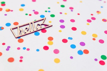 wooden letters Hello with colorful confetti on white background