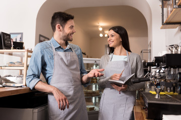 Emotional couple pointing on coffee machine and smiling.