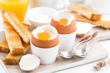 boiled eggs and toasts on a wooden board