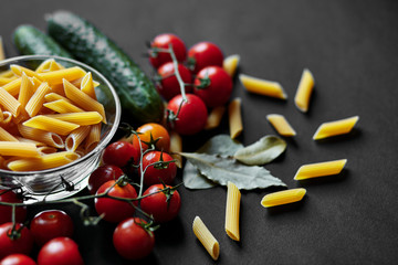 Still life with pasta, cherry tomatoes and cucumbers. The texture of pasta. Vegetables. Italian Pasta. Place for your advertising.