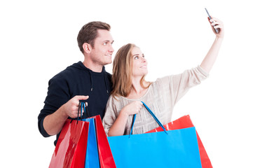 Couple taking selfie and holding shopping bags