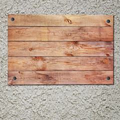 Vintage wooden sign on gray stucco concrete wall.