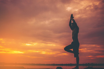 Silhouette of young man doing yoga at sunset.