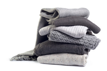 Stack of various sweaters isolated on white background