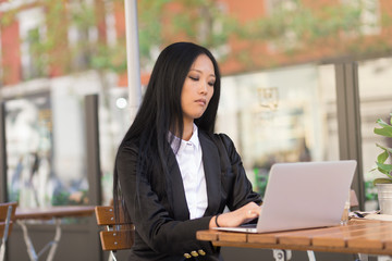 Asian middle-aged businesswoman working at a cafe table