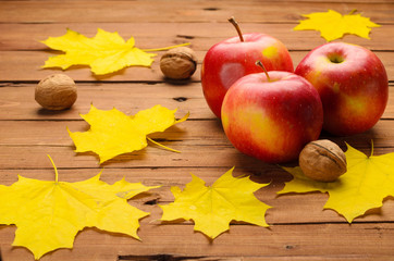 Fresh apples, walnuts and yellow maple leaves on old wooden tabl